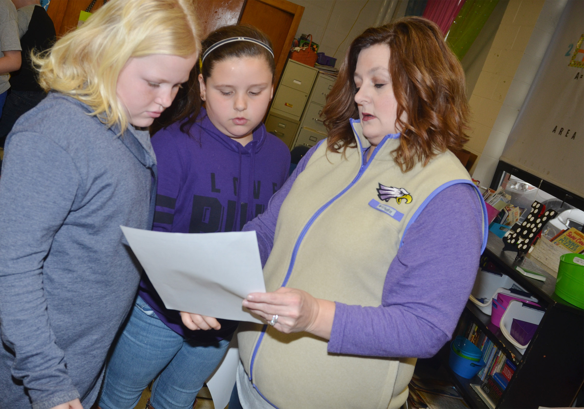CMS fifth-grade teacher Garnetta Murrell helps Daisy Wilkerson, at left, and Kaitlyn Keith with fractions.