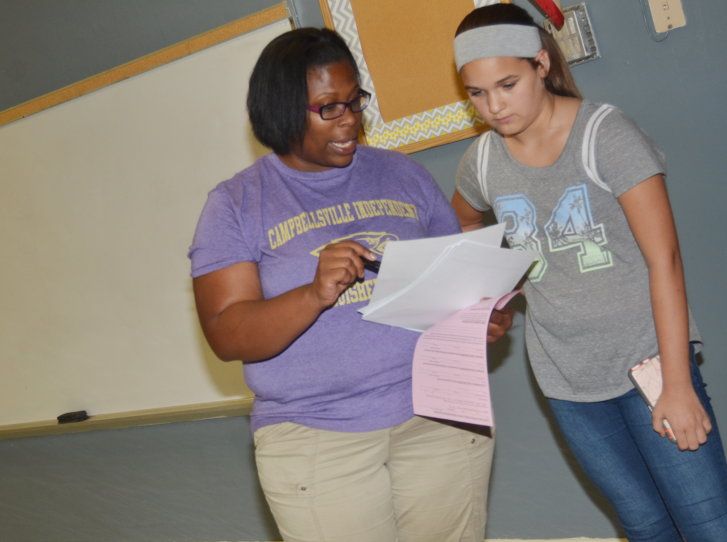 CMS teacher Tiarra Cecil looks over this year's schedule with seventh-grader Kailey Lozano.