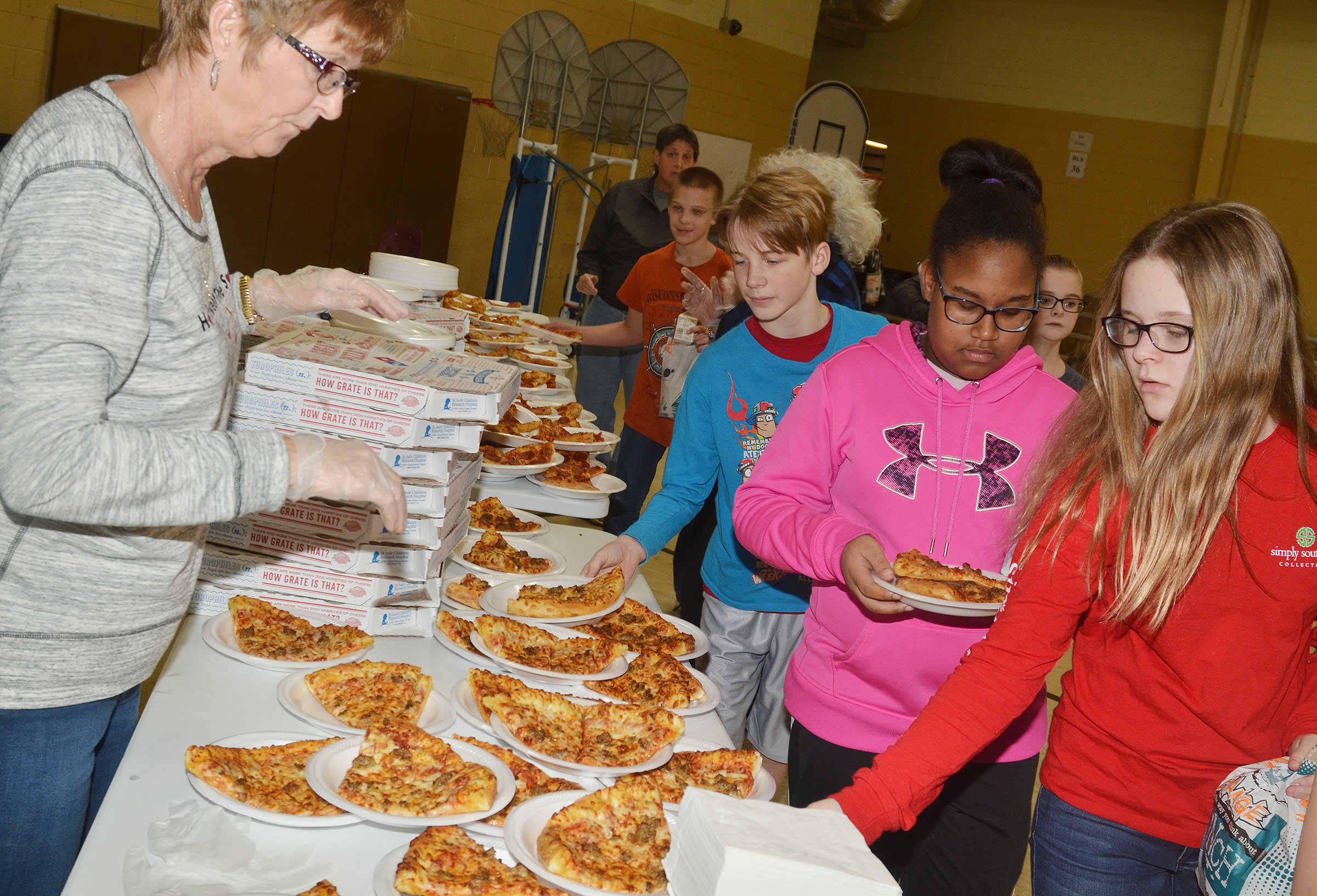 CMS assistant Carolyn Gaskins serves pizza.