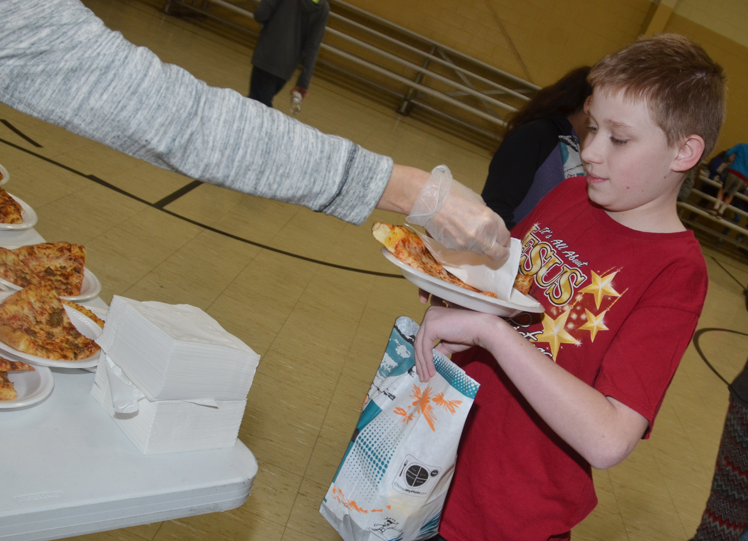 CMS sixth-grader Willie Nunn is served pizza.