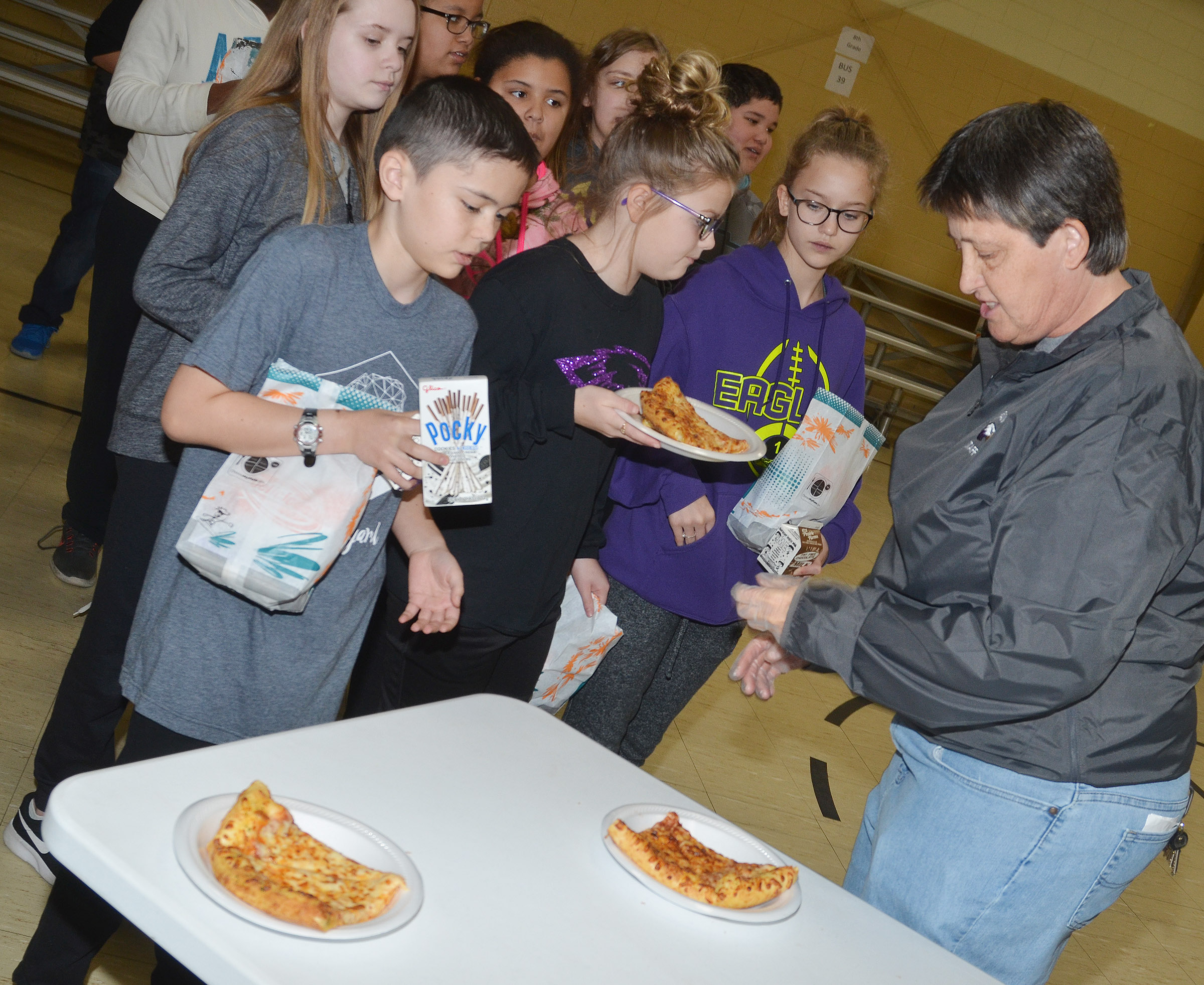 CMS exceptional child educator Katie Wilkerson serves pizza.