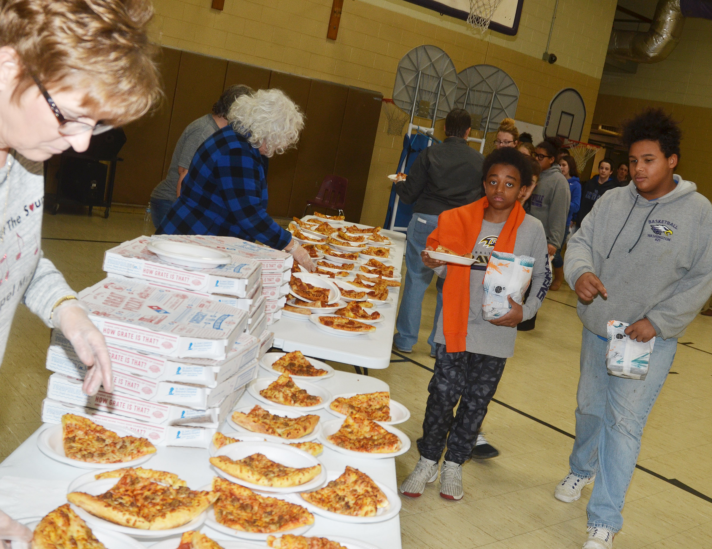 CMS seventh-graders Zamar Owens, at left, and J.T. Washington are served pizza.