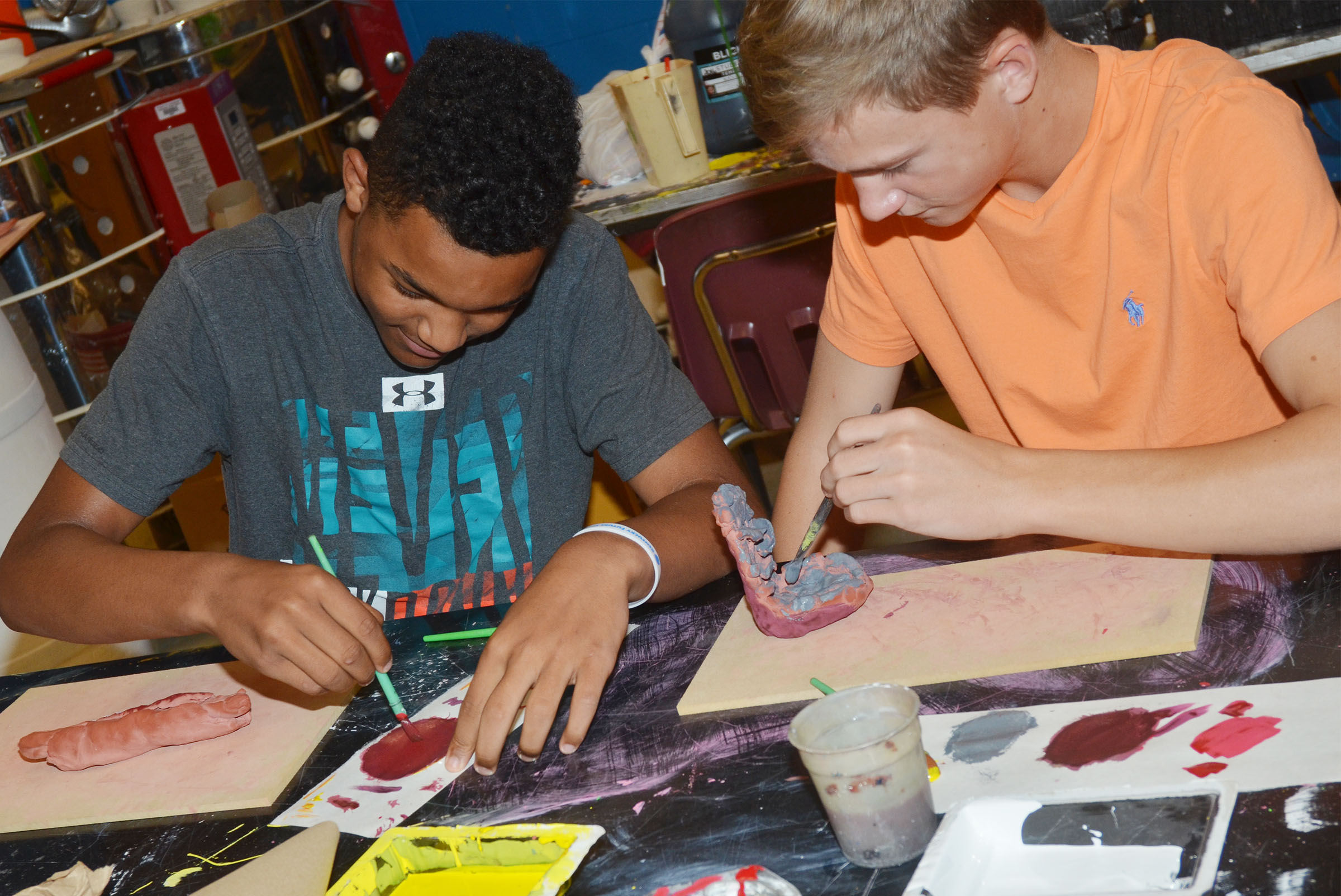 CMS eighth-graders Reggie Thomas, at left, and Blase Wheatley paint their creations.