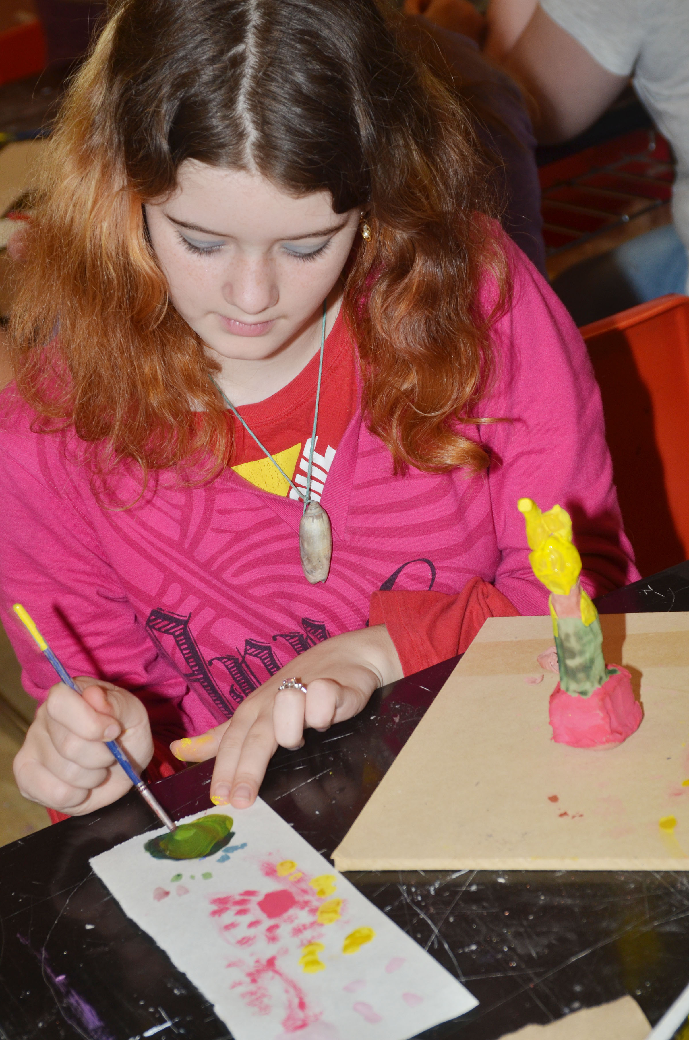 CMS sixth-grader Leah Parker paints her pottery.