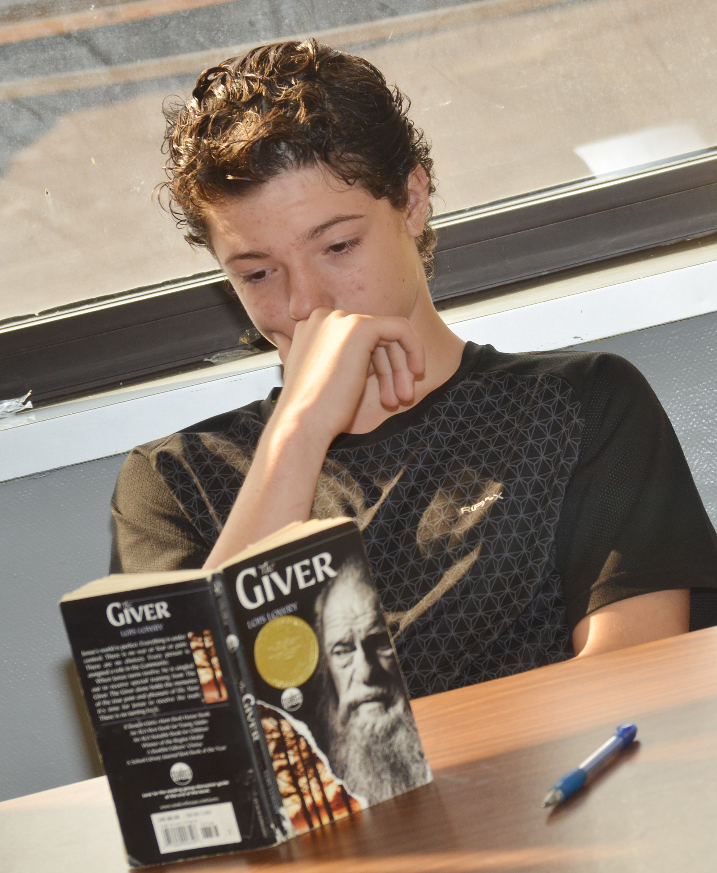 "CMS eighth-grader C.J. Adams reads ""The Giver."""