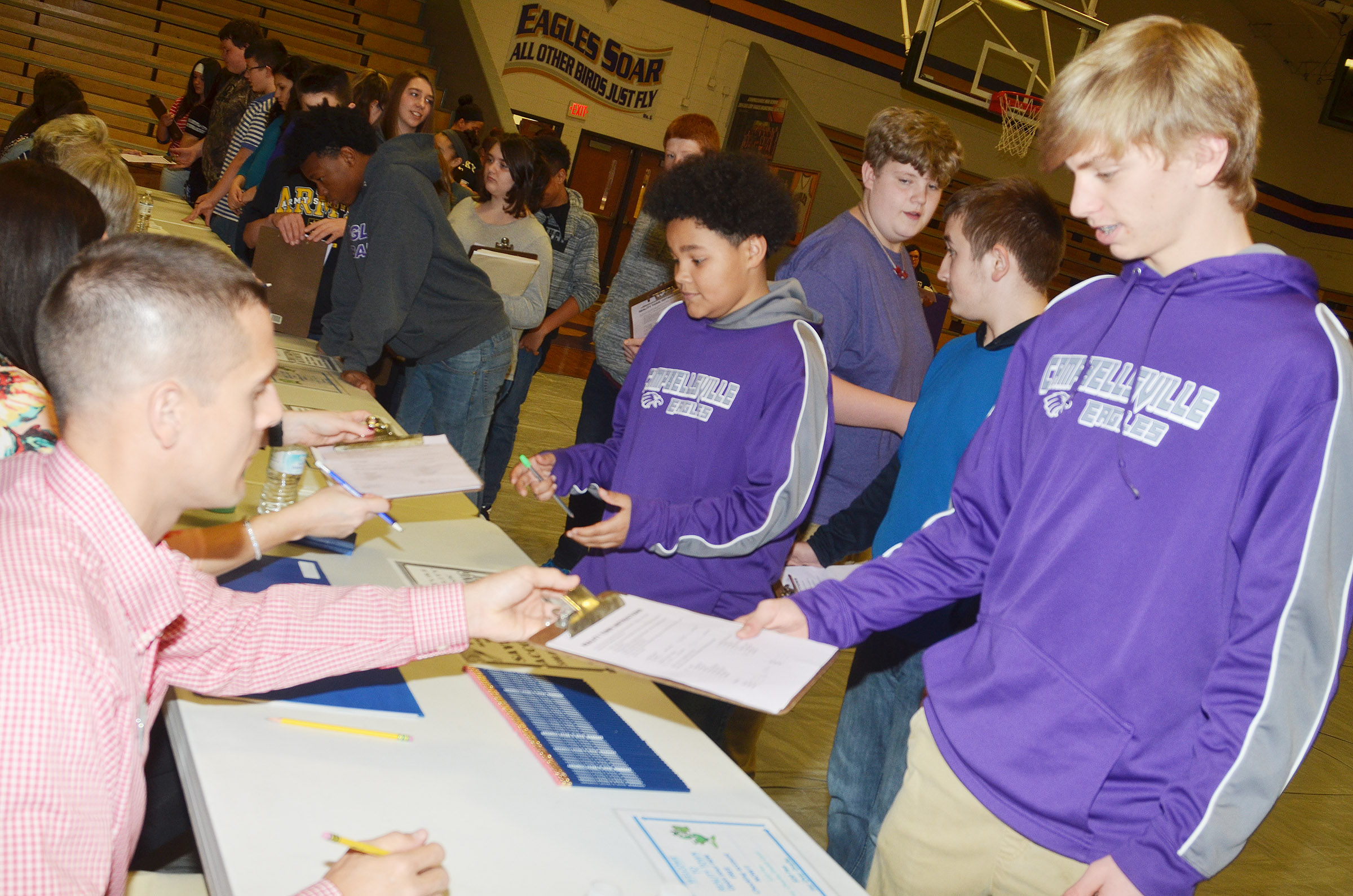 CMS eighth-grader Arren Hash, at right, and his classmates receive their checking account information, with a balance showing what they might make when they work in their chosen career.