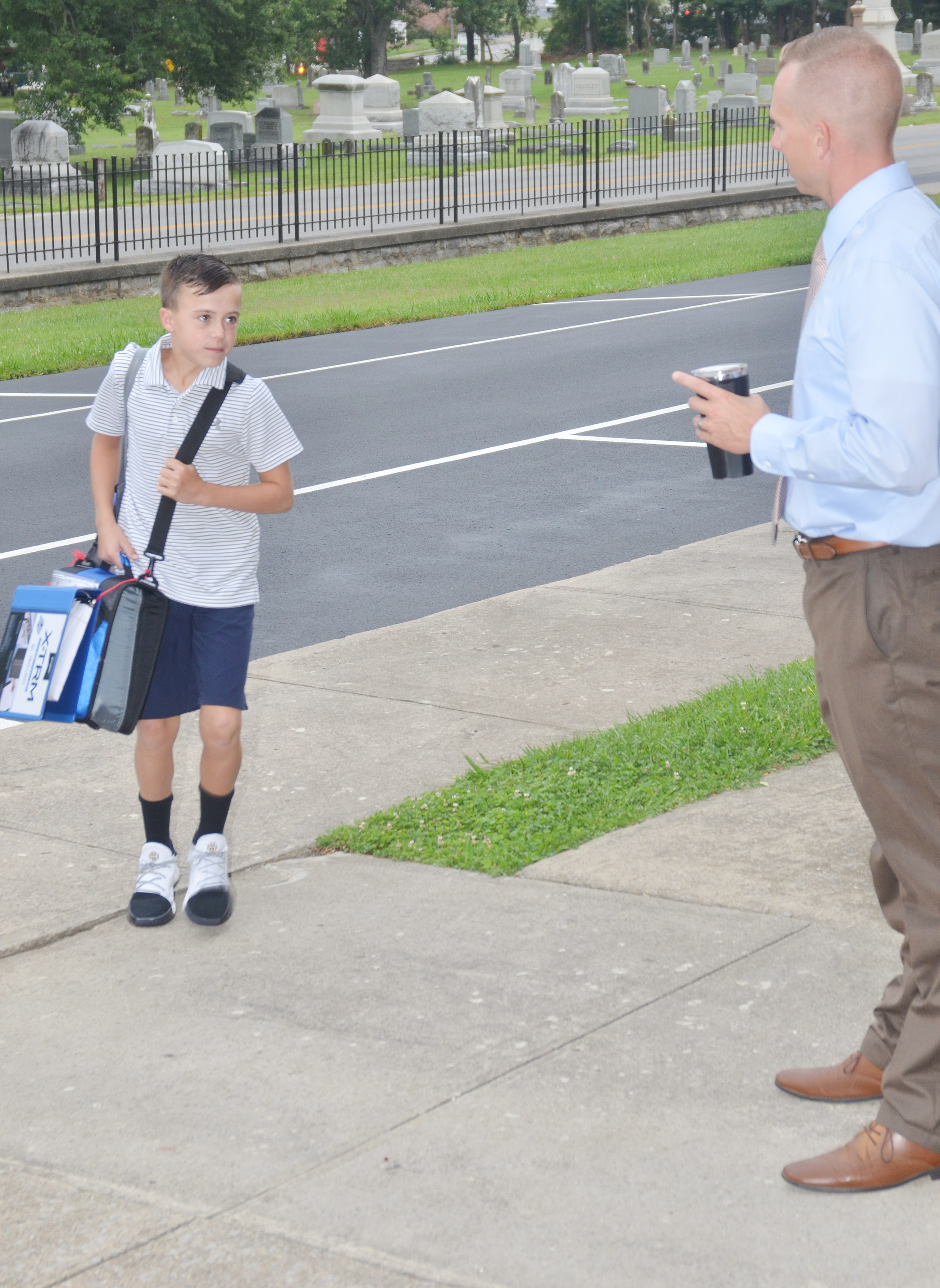 CMS Principal Zach Lewis greets Chase Hord on his second day of seventh grade.