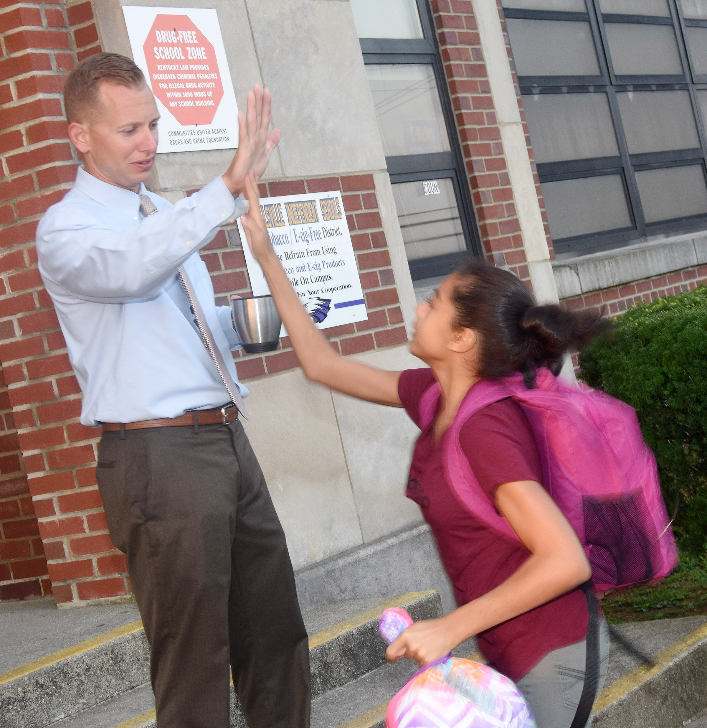 CMS Principal Zach Lewis high-fives sixth-grader Falicity Lewis as she comes to school.
