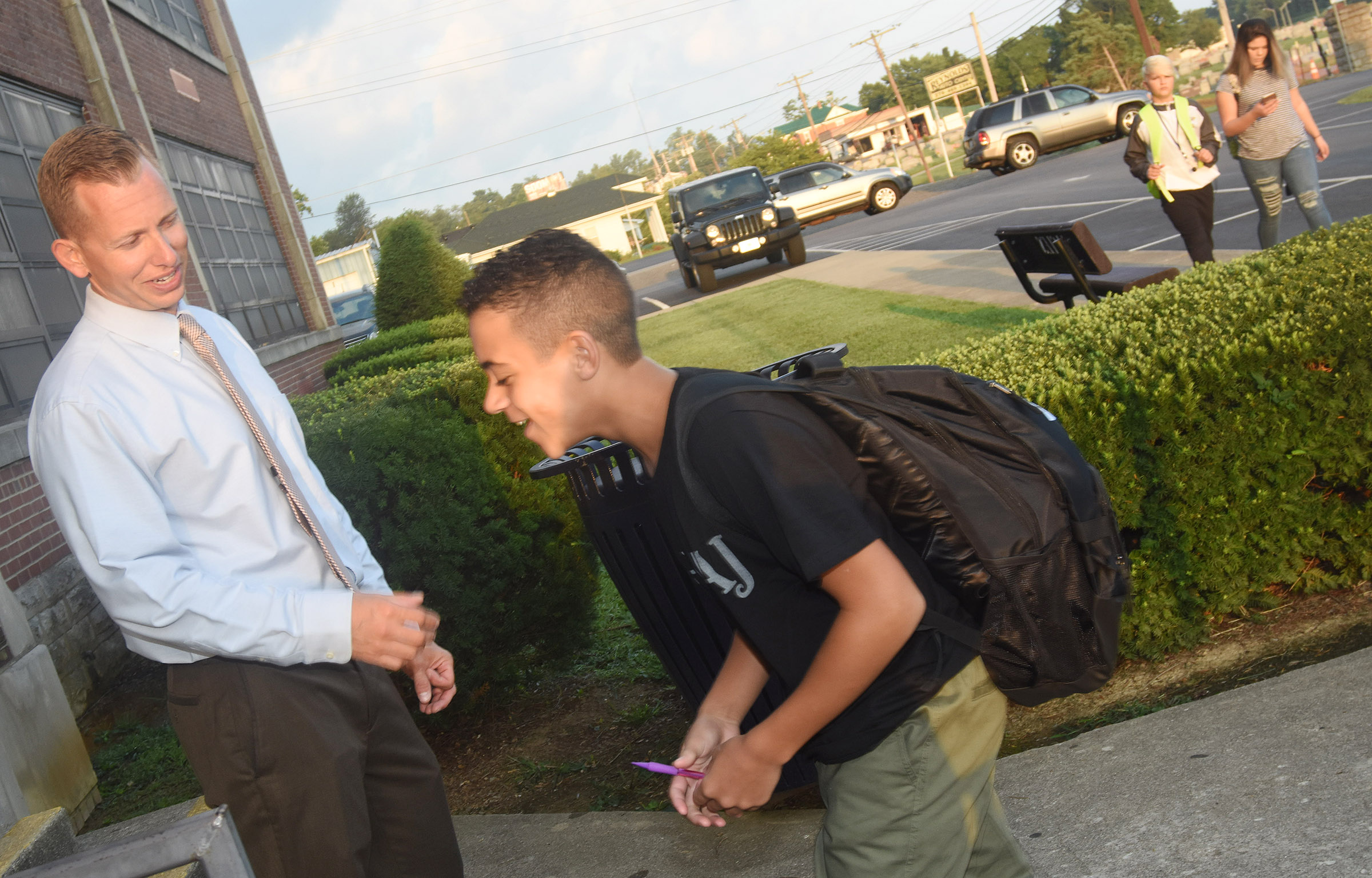 CMS Principal Zach Lewis greets seventh-grader Tucker Cartwright as he walks in for school.