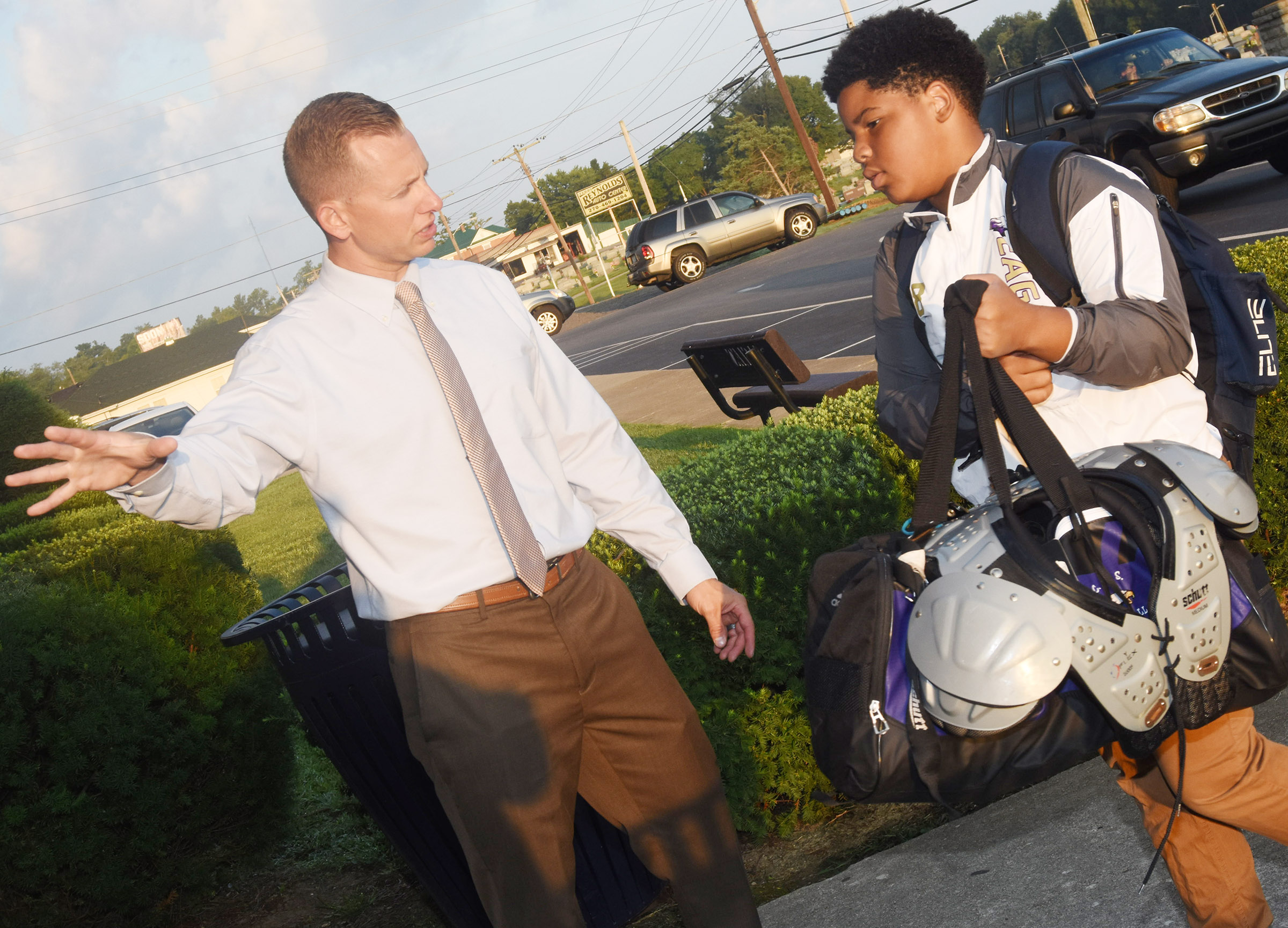 CMS Principal Zach Lewis talks to seventh-grader Devin Kinser as he walks in for school.