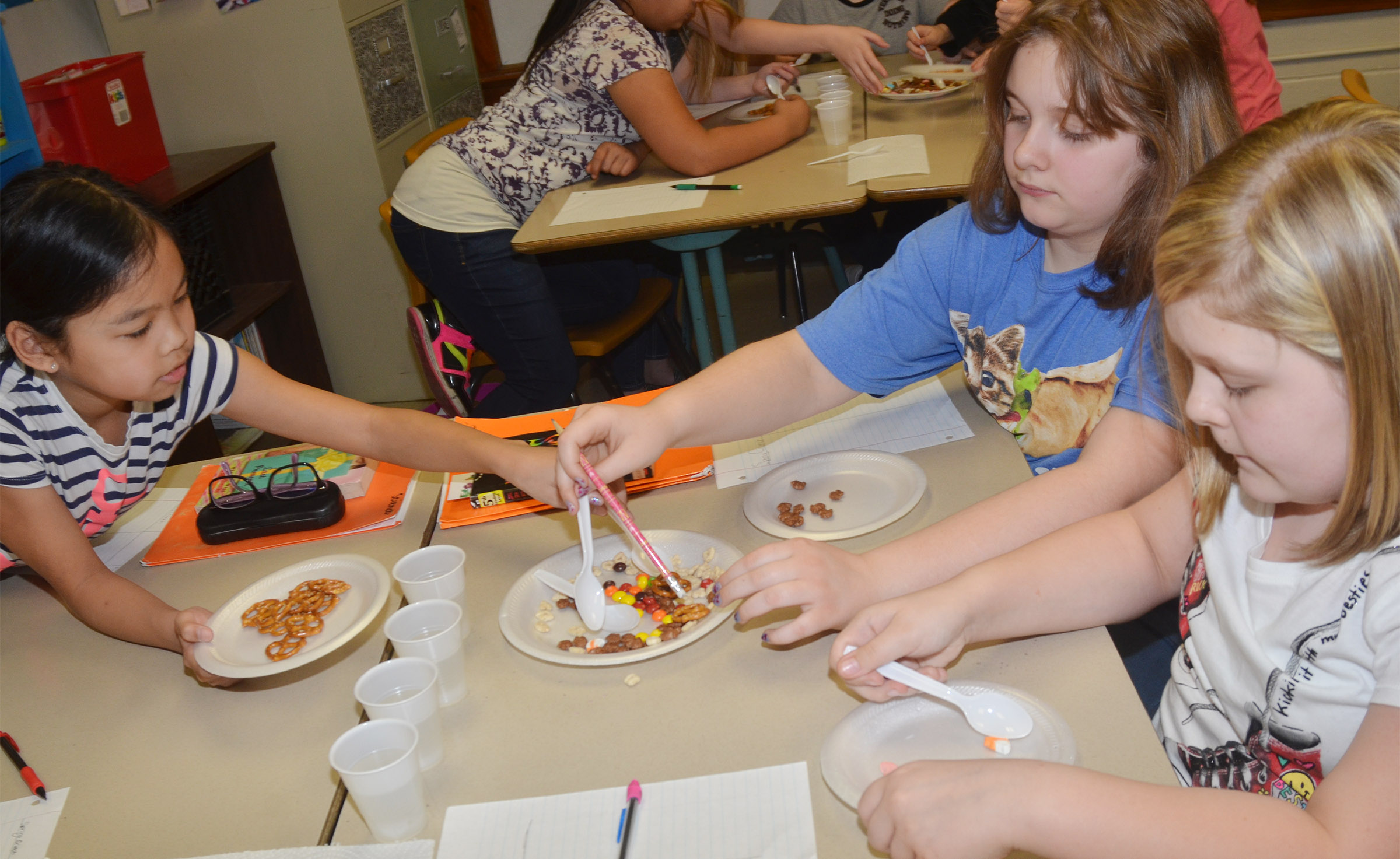 CMS fifth-graders, from left, Angelica Seng, Lexi Garvin and Alexis Sharp separate their mixture of snack foods.