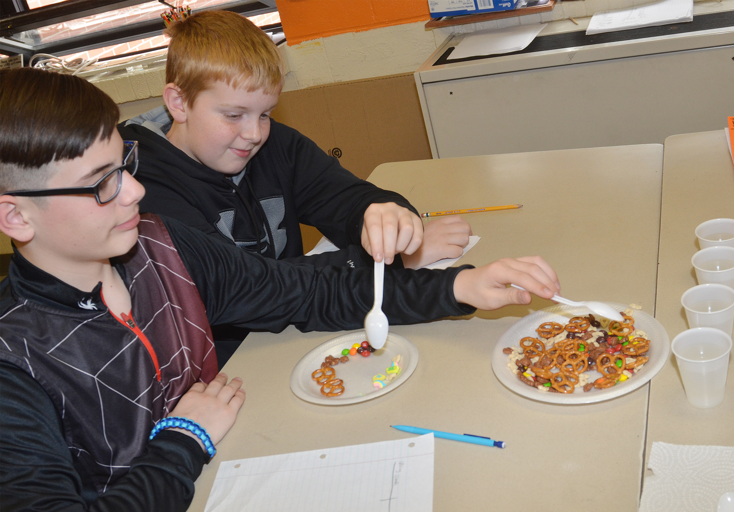 CMS fifth-graders Isaac Garrison, at left, and Ryder Cundiff separate their mixture of snack foods.
