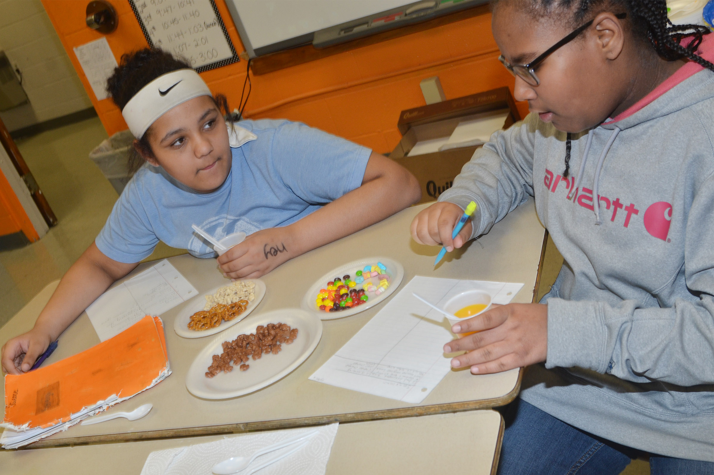 CMS fifth-graders Kehleigh Vaught, at left, and KyAshia Mitchell discuss the differences between mixtures and solutions.