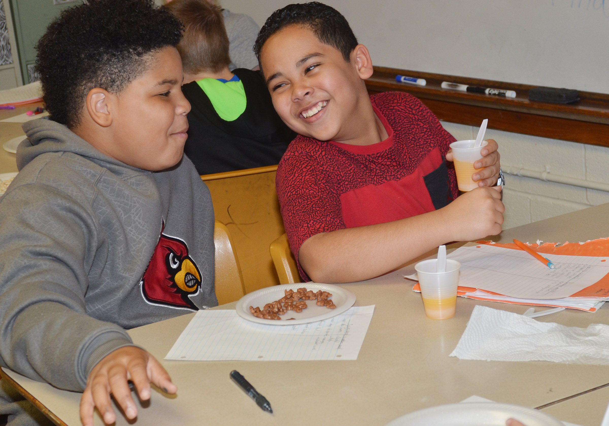 CMS fifth-graders Devin Kinser, at left, and Diego Noyola laugh as they enjoy their orange drink.