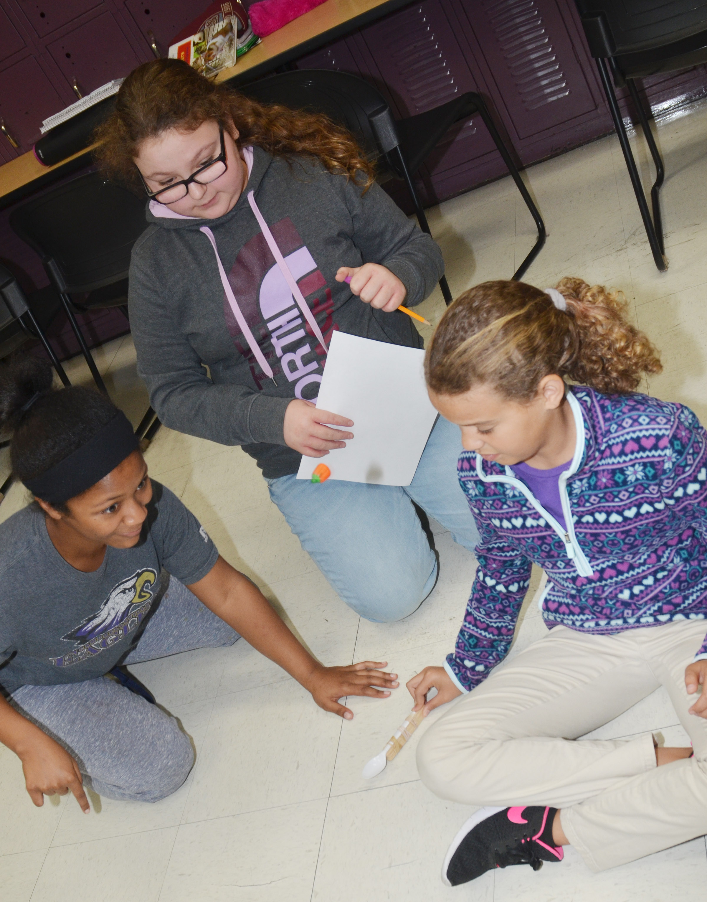 From left, CMS sixth-graders Camilla Taylor, Chloe Mitchell and Arisha Francis launch their catapult.