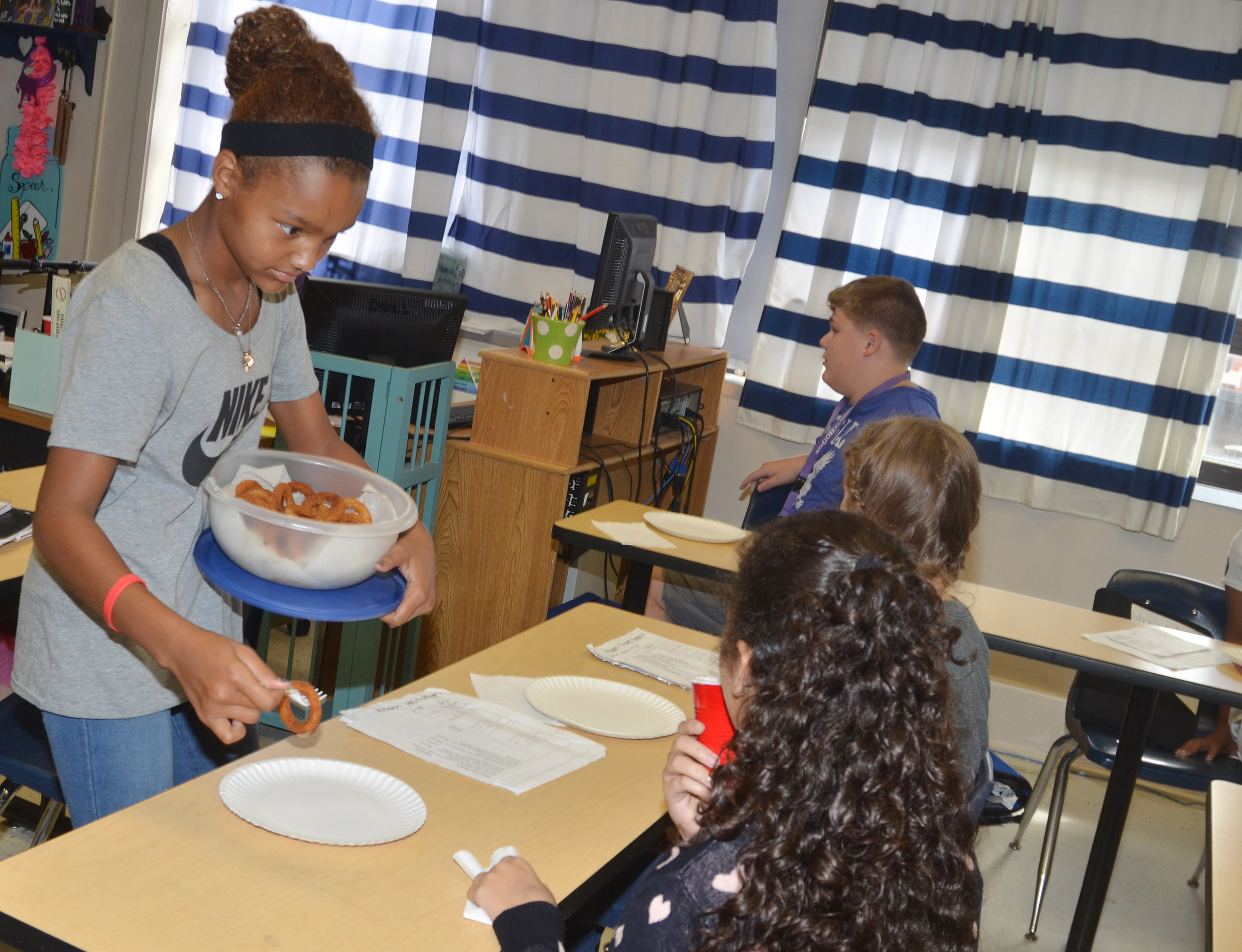 CMS eighth-grader Alexis Thomas passes out onion rings, a food originating from the western region.