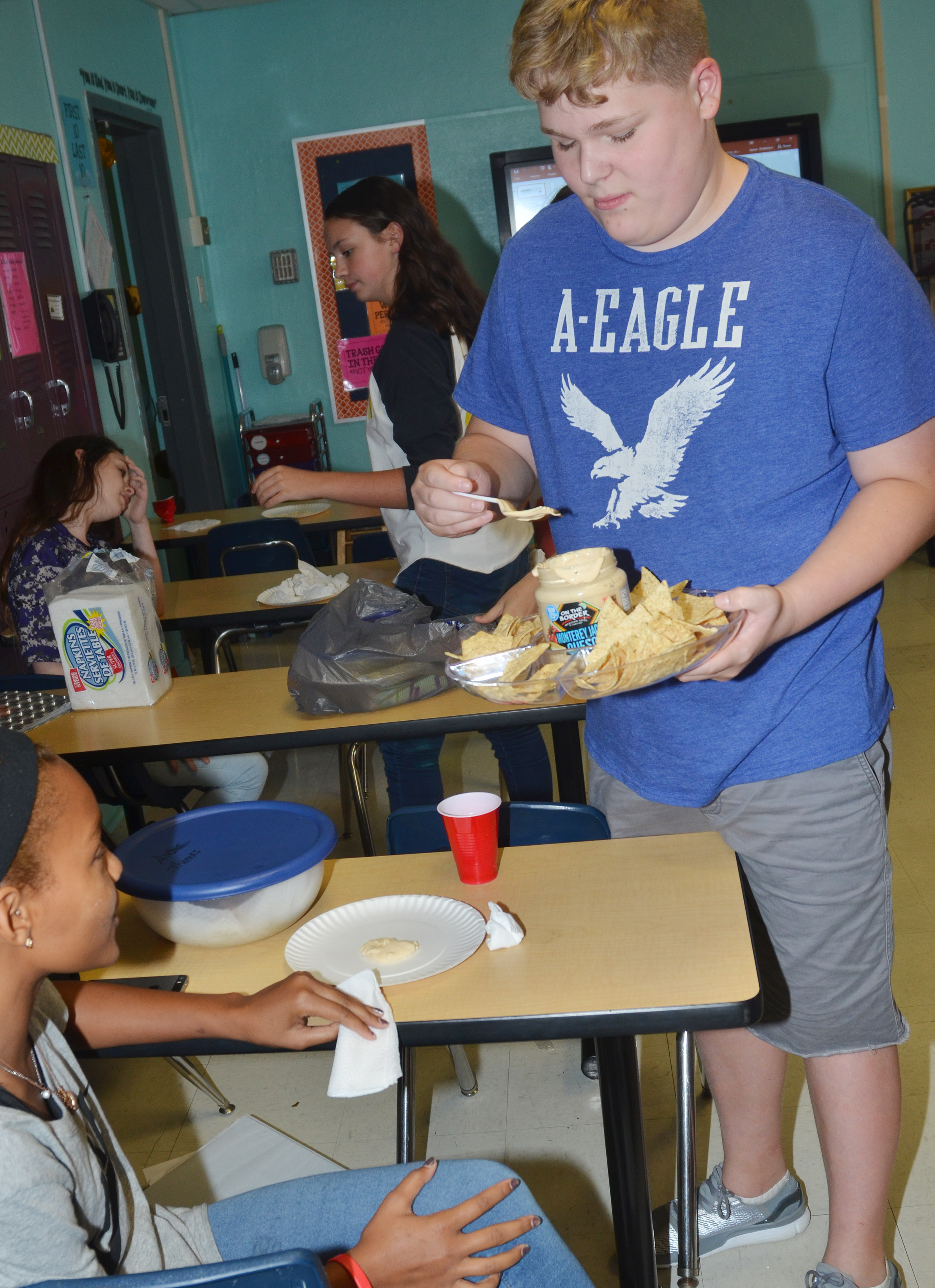 CMS eighth-grader Blake Settle passes out chips and queso dip, which originates from the southwest region.