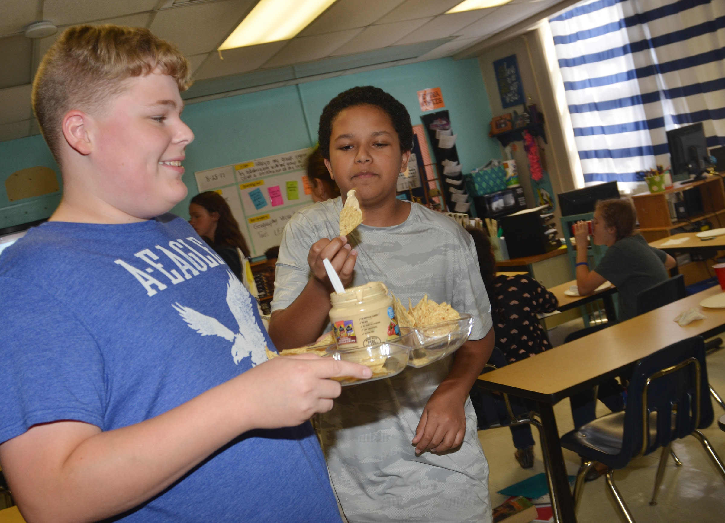 CMS eighth-grader Blake Settle passes out chips and queso dip, which originates from the southwest region, as classmate Tezon Mitchell samples a chip.
