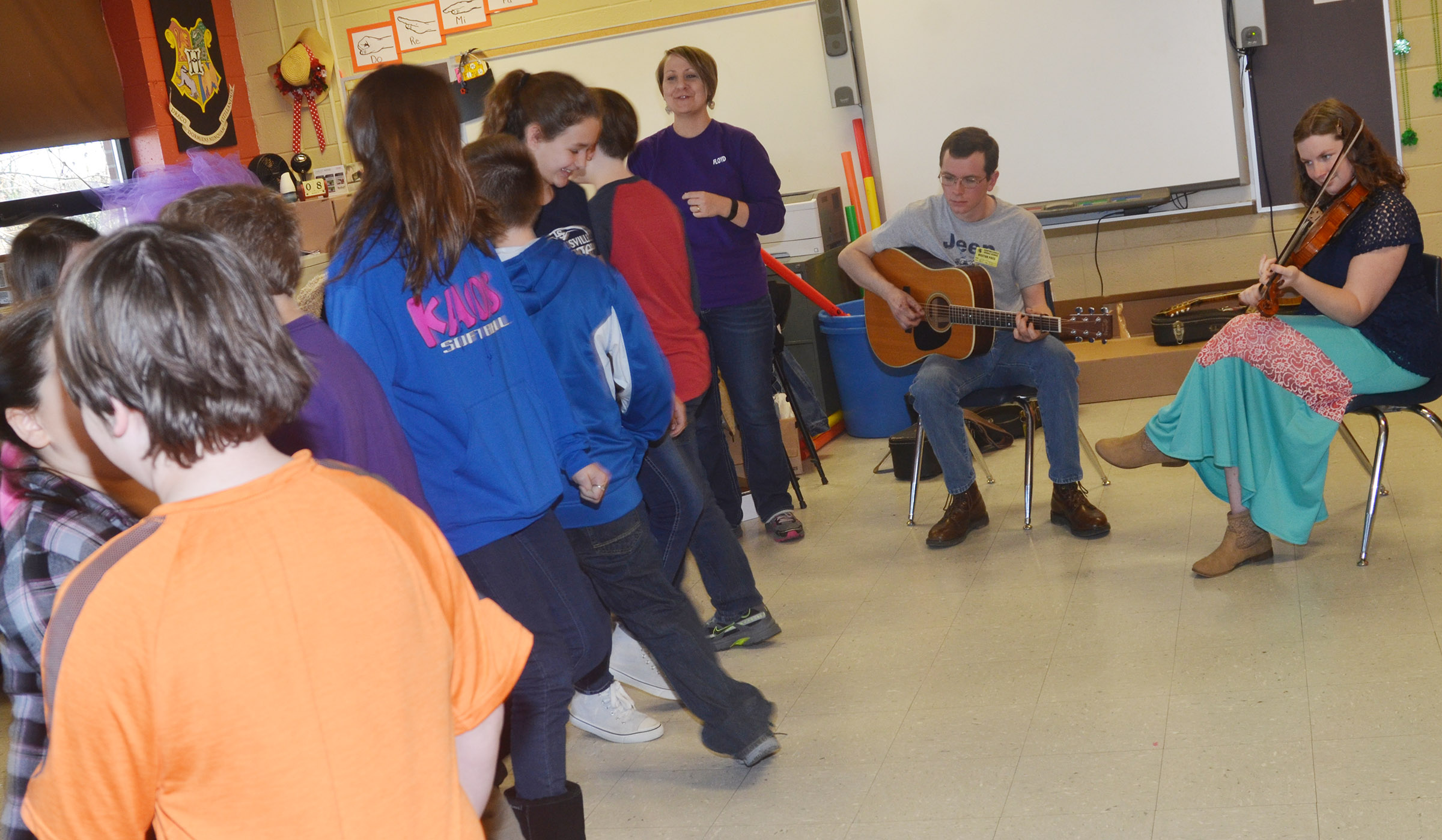 Local musicians Alex Vaughn, at left, and Jenny Beams play folk music as CMS students, led by music teacher Jessica Floyd, try out square dancing.