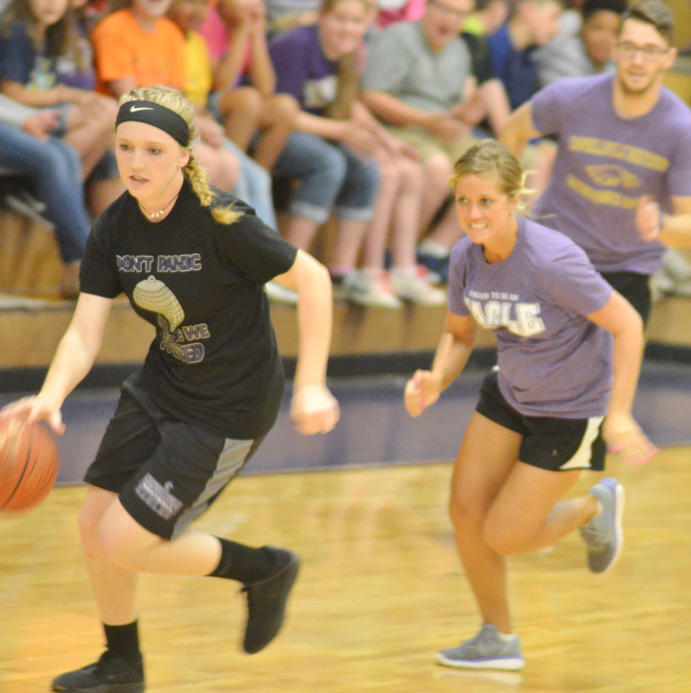 CMS eighth-grader Catlyn Clausen dribbles to the basket as bookkeeper Natalia Warren runs after her.