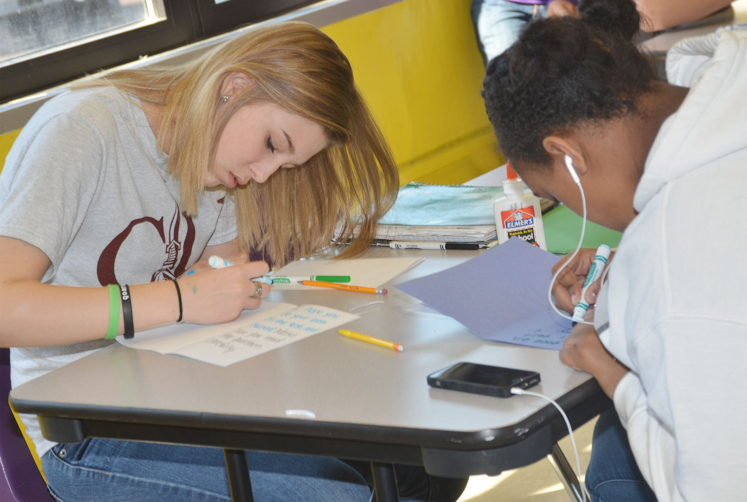 CMS eighth-graders Autumn Harvey, at left, and Kelsey King write good luck cards for their classmates.