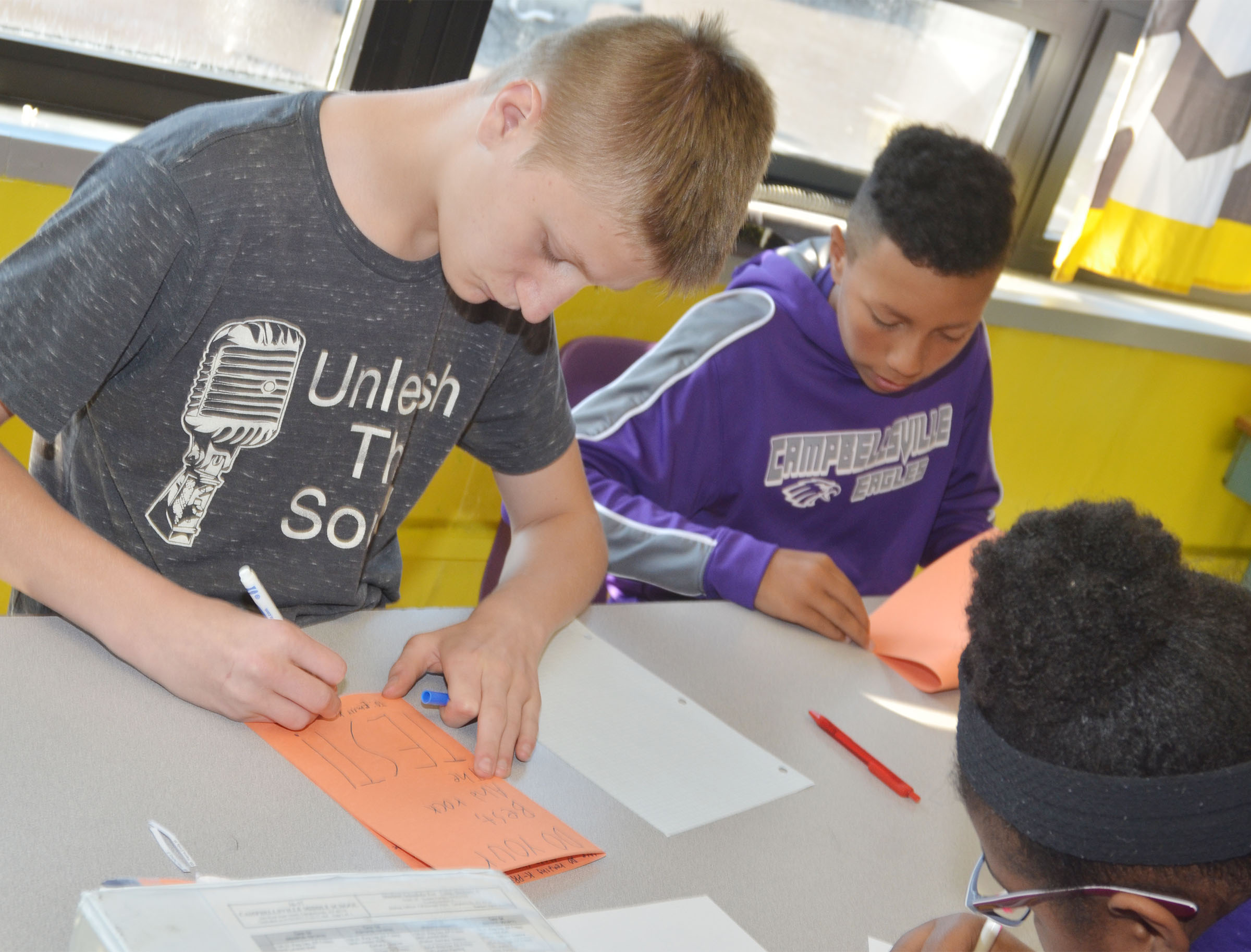 CMS eighth-graders Jake Dicken, at left, and Jastyn Shively write good luck cards for their classmates.