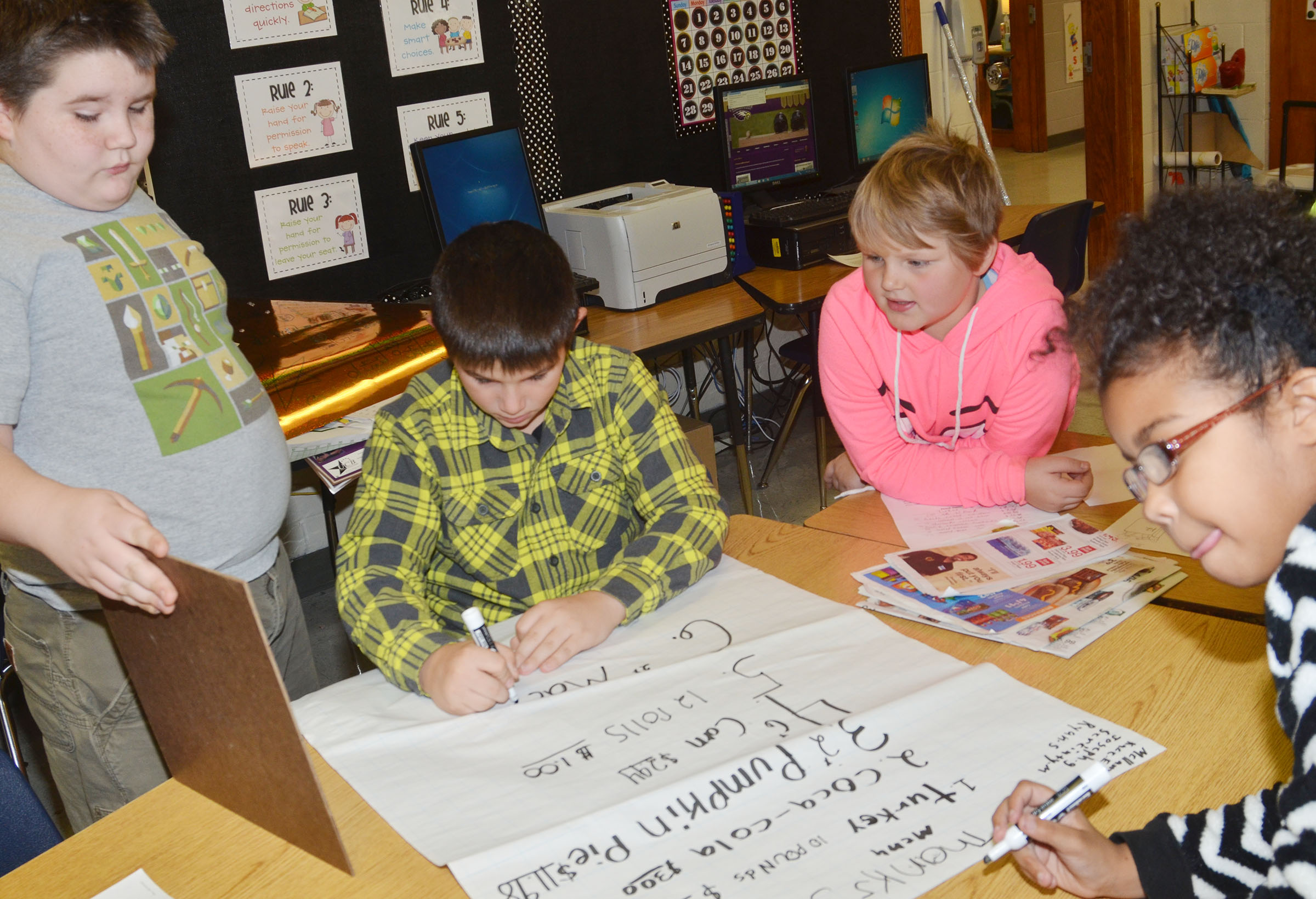 CMS fourth-graders, from left, Joseph Gutierrez, Kace Eastridge, Mellany Parker and Serenity Mings discuss how much their Thanksgiving dinner will cost.