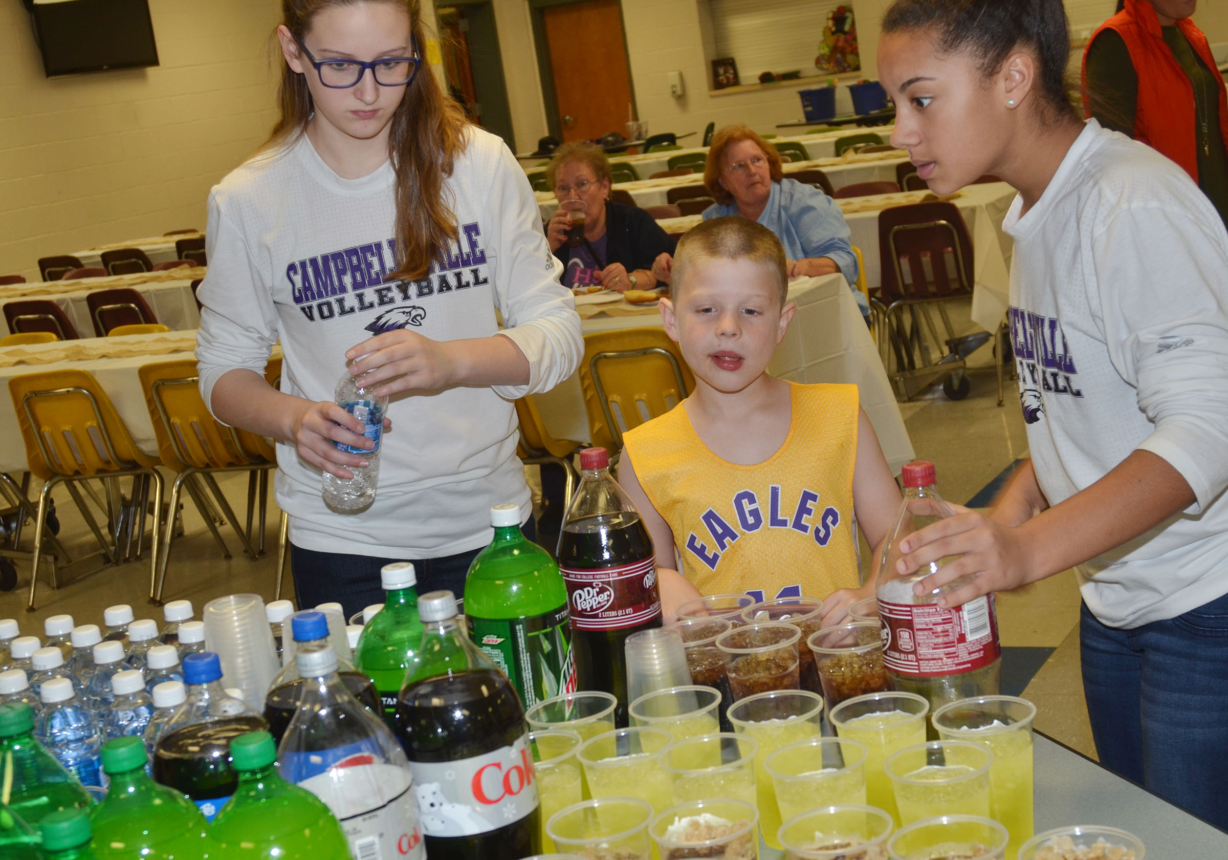 CMS volleyball players Zoie Sidebottom, at left, and Laci Hodgens, eighth-graders, serve Campbellsville Elementary School first-grader Brody Sidebottom a drink.