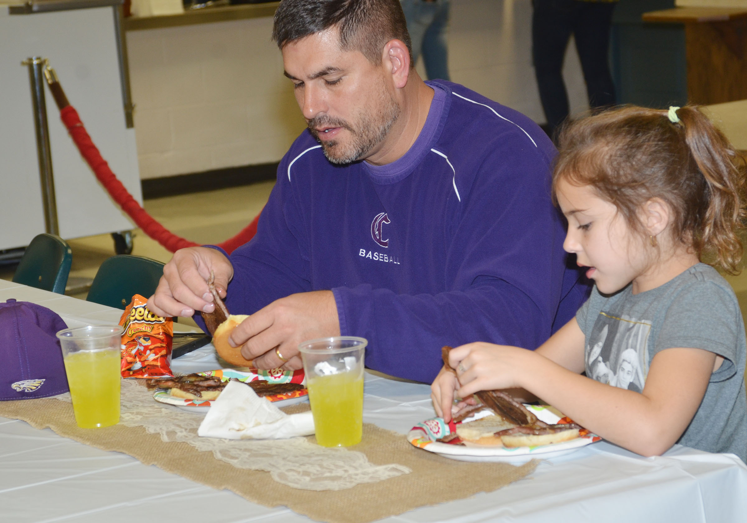 CHS Principal Kirby Smith and his daughter, Karsyn, eat a barbecue dinner together.