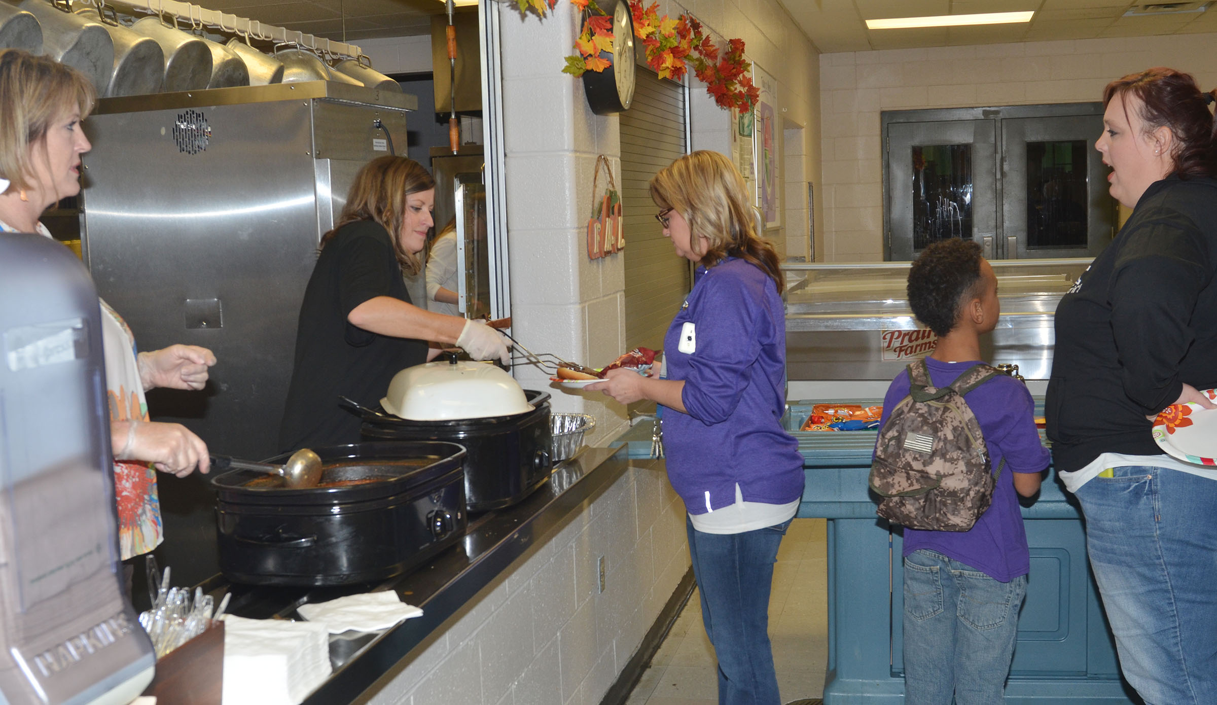 CMS volleyball mothers Andrea Smith, at left, and Ashlee Petett serve barbecue.
