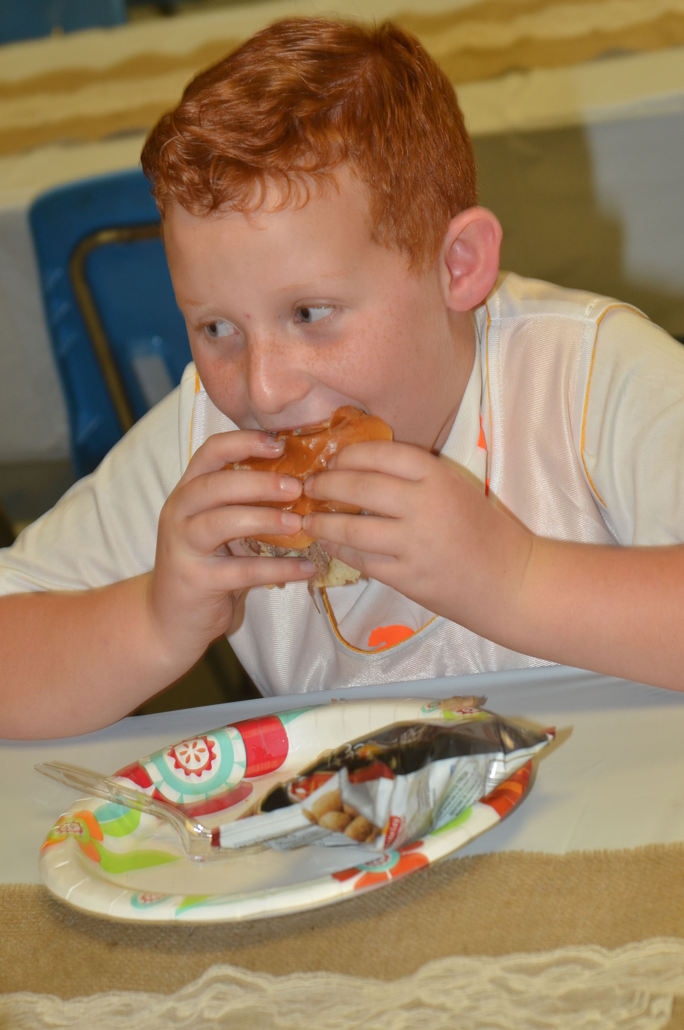 Campbellsville Elementary School second-grader Reece Swafford takes a bite of his barbecue sandwich.