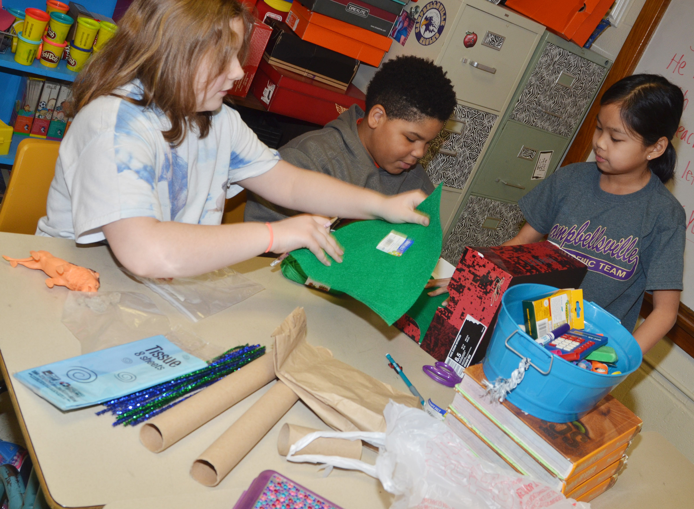 From left, CMS fifth-graders Lexi Garvin, Devin Kinser and Angelica Seng work together to make their model.