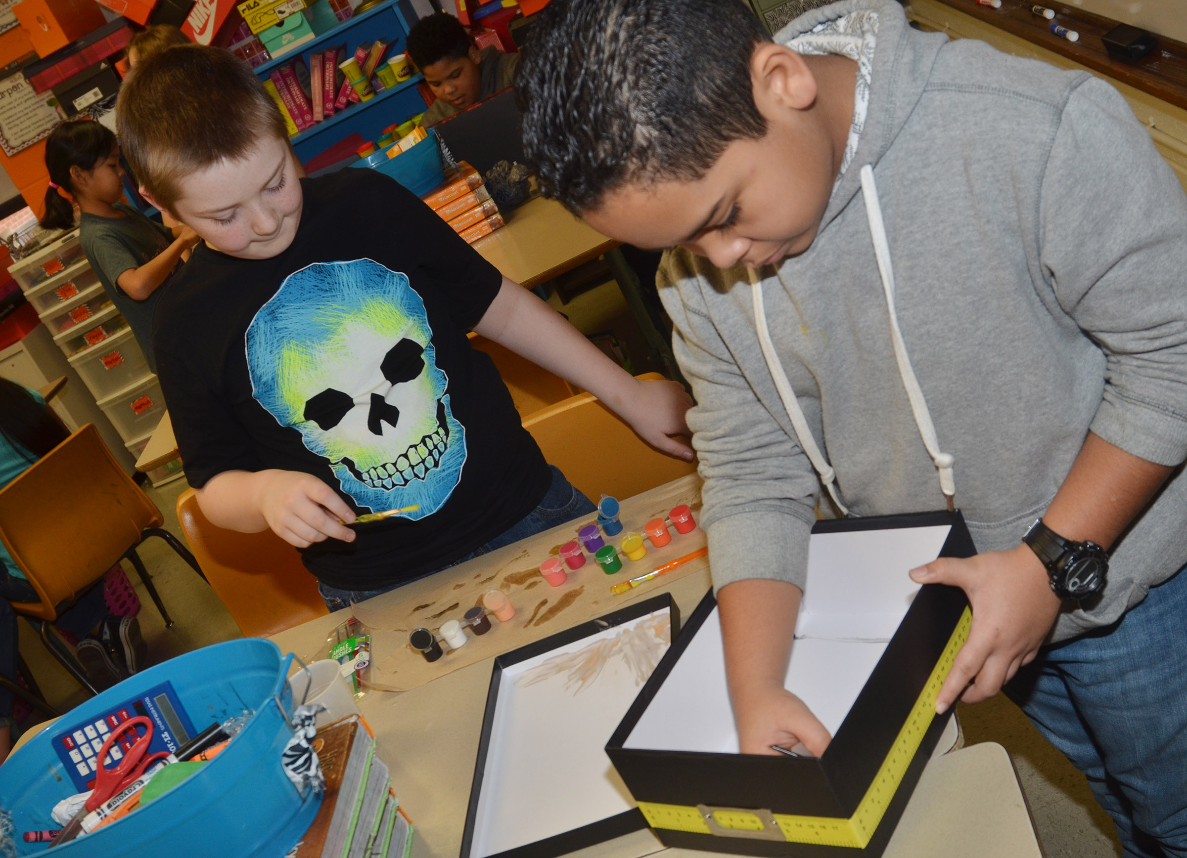 CMS fifth-graders Sully Streeval, at left, and Diego Noyola paint their model.