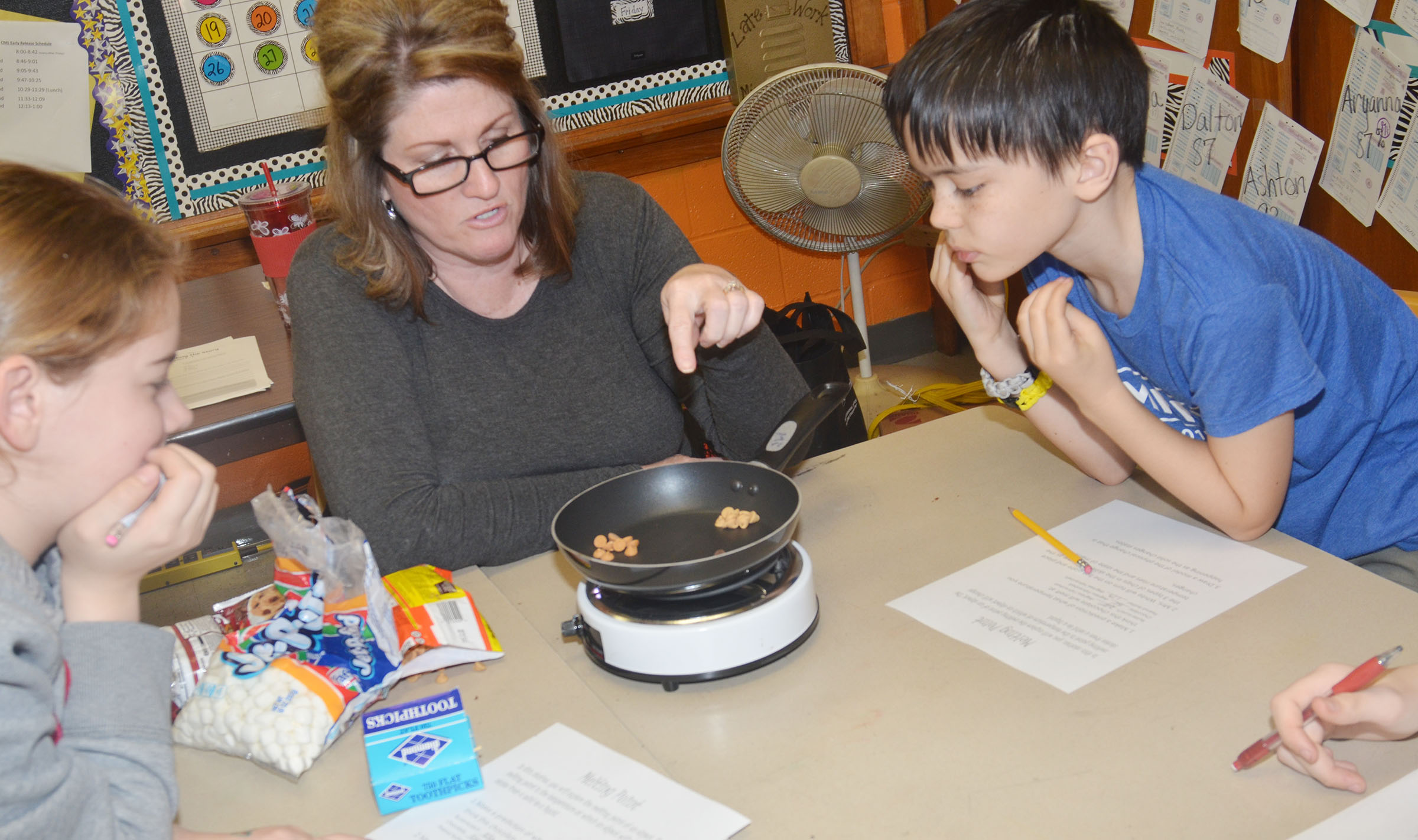 CMS fifth-grade teacher Donna White helps students Layla Steen, at left, and Isacc Billeter understand why different types of baking chips melt at different temperatures.
