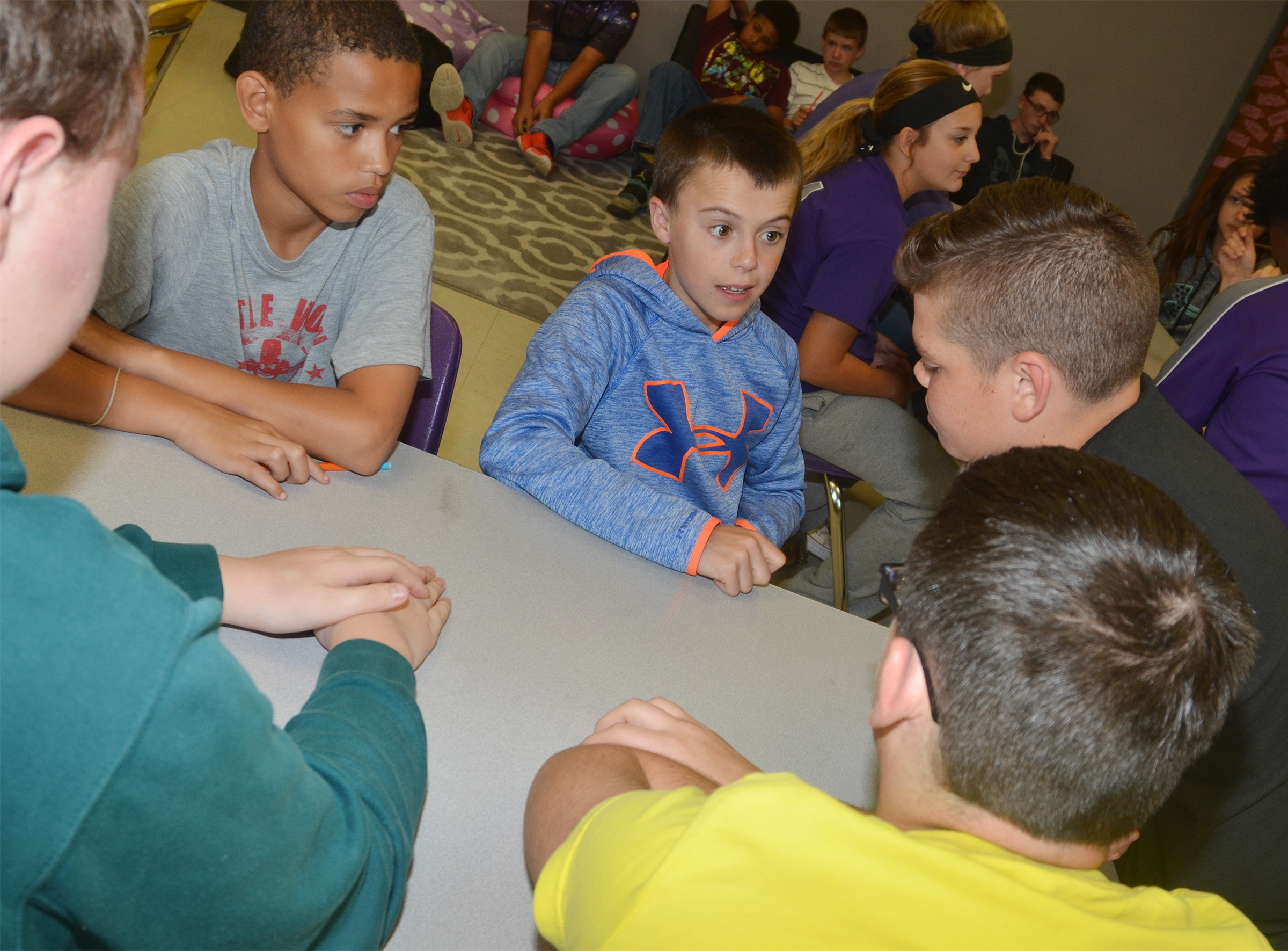 CMS sixth-graders Nasir Johnson, at left, and Chase Hord talk with their teammates about a question.