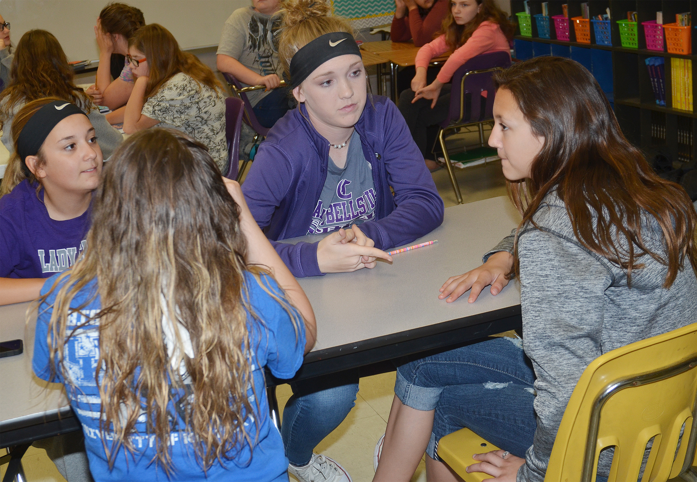 CMS sixth-grader Briana Davis, at left, and eighth-grader Catlyn Clausen talk with their teammates about a question.